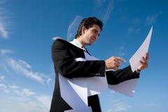 Geschäftsmann, der über Schreibarbeit schaut Lizenzfreie Stockbilder
