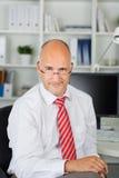 Geschäftsmann, der über seinen Gläsern schaut Stockfotos