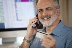 Geschäftsmann, der über Telefon mit Kreditkarte zahlt Stockfotografie