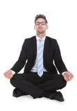Geschäftsmann, der über weißem Hintergrund meditiert Stockbilder