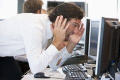 Geschäftsmann, der Überwachungsgerät entsetzt betrachtet Stockfoto