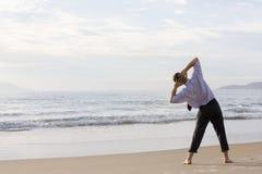 Geschäftsmann, der Übungen auf Strand tut Lizenzfreie Stockfotos