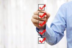Geschäftsmann, der Abschlussnote auf Checkliste überprüft Stockbilder