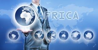 Geschäftsmann, der Afrika-Kontinent auf virtuellem digitalem Schirm wählt Lizenzfreie Stockfotos