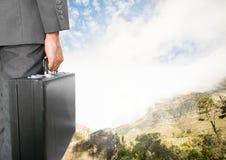 Geschäftsmann, der Aktenkoffer unter Himmelwolken und -Berglandschaft hält Lizenzfreies Stockfoto