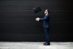 Geschäftsmann, der Aktenkoffer wirft stockfotos