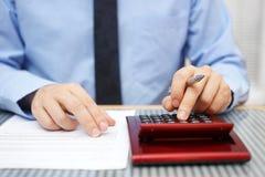 Geschäftsmann, der Artikel der Vereinbarung berechnet und überprüft Stockbild
