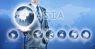 Geschäftsmann, der Asien-Kontinent auf virtuellem digitalem Schirm wählt stockfotografie