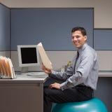 Geschäftsmann, der auf Übungskugel am Schreibtisch sitzt Stockfotos