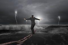 Geschäftsmann, der auf alter Eisenkette mit dunklem stürmischem Ozean balanciert Stockfoto