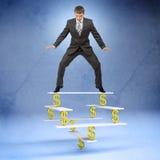 Geschäftsmann, der auf Balance mit Dollarzeichen steht Lizenzfreie Stockbilder