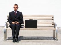 Geschäftsmann, der auf Bank sitzt Stockfoto