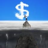 Geschäftsmann, der auf Bergspitze für Dollarzeichen-Form clou zujubelt Lizenzfreie Stockfotos