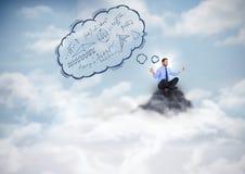 Geschäftsmann, der auf Bergspitze mit blauer Gedankenwolke meditiert Stockfotografie