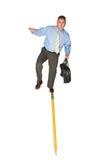 Geschäftsmann, der auf Bleistift balanciert Lizenzfreies Stockfoto