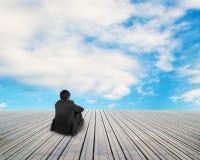 Geschäftsmann, der auf Bretterboden mit Wolke und blauem Himmel sitzt lizenzfreie stockfotos