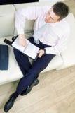 Geschäftsmann, der auf Couch sitzt Stockbild