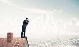 Geschäftsmann, der auf Dach steht und in den Ferngläsern schaut Misch ich Lizenzfreies Stockbild