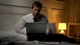Geschäftsmann, der auf dem Computer, online beraten mit Partner, Nachtarbeit simst stockbilder