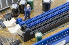 Geschäftsmann, der auf dem Computermotherboard steht Lizenzfreie Stockbilder