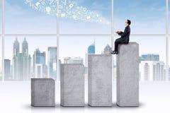 Geschäftsmann, der auf dem höchsten Diagramm sitzt Stockbilder