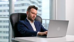 Geschäftsmann, der auf dem Laptop im Büro schreibt stock footage