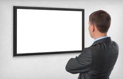 Geschäftsmann, der auf dem leeren Bildschirm schaut Stockbild