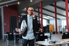Geschäftsmann, der auf dem Mobiltelefon und den tragenden Mappen spricht Stockfoto