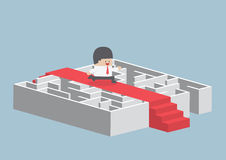 Geschäftsmann, der auf dem roten Teppich über dem Labyrinth läuft lizenzfreie abbildung