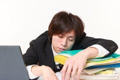 Geschäftsmann, der auf dem Schreibtisch schläft Lizenzfreie Stockfotografie