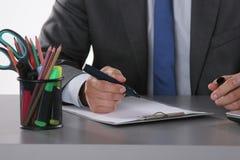 Geschäftsmann, der auf dem Schreibtisch sitzt und in seinem Büro arbeitet Stockbild