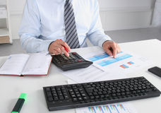 Geschäftsmann, der auf dem Schreibtisch sitzt und in seinem Büro arbeitet Lizenzfreie Stockfotografie