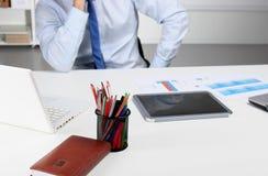 Geschäftsmann, der auf dem Schreibtisch sitzt und in seinem Büro arbeitet Lizenzfreies Stockbild