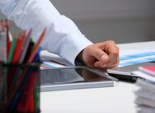 Geschäftsmann, der auf dem Schreibtisch sitzt und in seinem Büro arbeitet Stockfotos