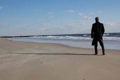 Geschäftsmann, der auf dem Strand denkt Lizenzfreie Stockfotografie
