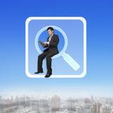 Geschäftsmann, der auf dem Suchen von APP-Ikone unter Verwendung der intelligenten Auflage sitzt Stockbild