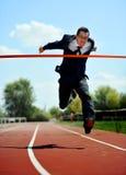 Geschäftsmann, der auf der athletischen Bahn feiert Sieg im Arbeitserfolgskonzept läuft Lizenzfreie Stockfotos