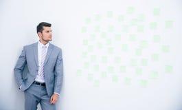 Geschäftsmann, der auf der Wand sich lehnt Stockbilder