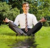 Geschäftsmann, der auf der Wiese sich entspannt Lizenzfreie Stockbilder