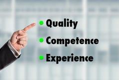 Geschäftsmann, der auf die Wörter, Qualität-Kompetenz-Experienc zeigt Stockbild