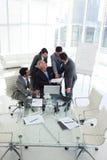 Geschäftsmann, der auf ein Dokument in einer Sitzung zeigt Stockbild