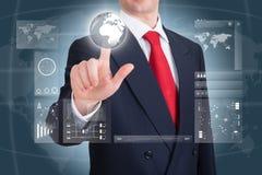 Geschäftsmann, der auf eine Erdkugel auf einem mit Berührungseingabe Bildschirm zeigt Lizenzfreie Stockfotografie