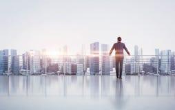 Geschäftsmann, der auf einem Dach steht und betrachtet Lizenzfreies Stockbild