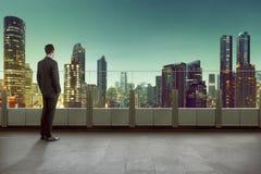 Geschäftsmann, der auf einem Dach steht und Stadt auf Nachtzeit betrachtet Lizenzfreie Stockfotografie