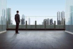 Geschäftsmann, der auf einem Dach steht und Stadt betrachtet Stockbild
