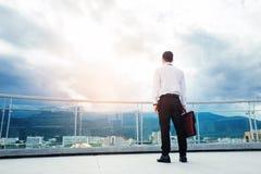 Geschäftsmann, der auf einem Dach steht und Stadt Erfolg und t betrachtet lizenzfreie stockfotos