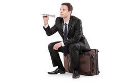 Geschäftsmann, der auf einem Gepäck sitzt Lizenzfreies Stockbild