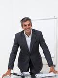 Geschäftsmann, der auf einem Konferenztische sich lehnt Stockfotografie