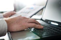 Geschäftsmann, der auf einem Laptop schreibt Stockfotos