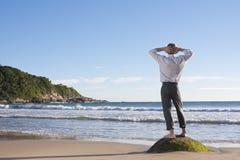 Geschäftsmann, der auf einem Strand sich entspannt stockfotografie
